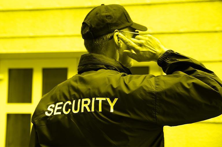 pracownik ochrony stojący przed budynkiem