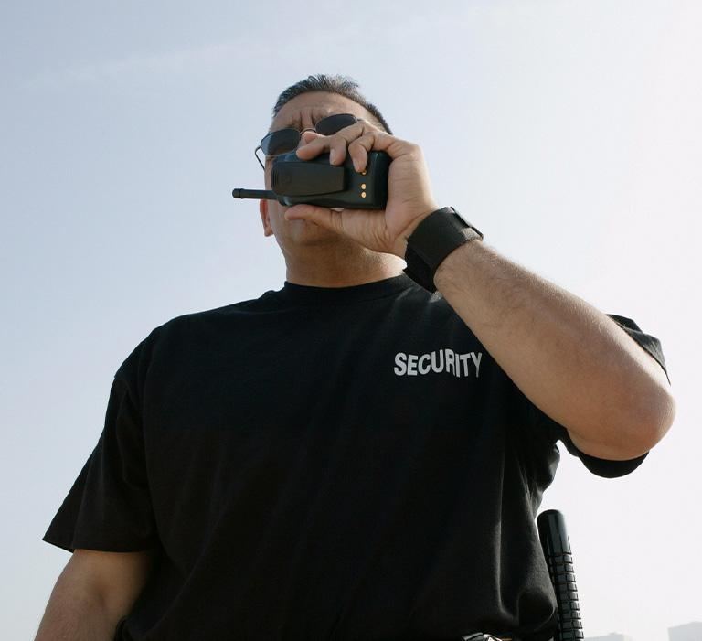 pracownik ochrony rozmawiający przez krótkofalówkę